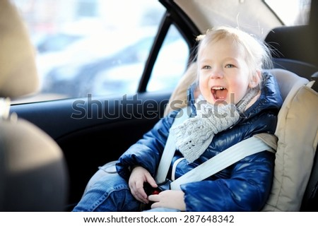 Adorable little girl sitting safely in a car seat - stock photo