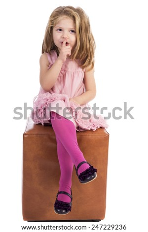 Adorable little girl sitting with legs crossed and making silence sign over white  - stock photo