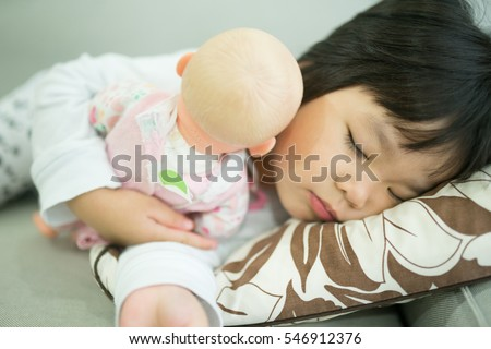 Adorable little girl sleep in the sofa bed and hug her baby doll.