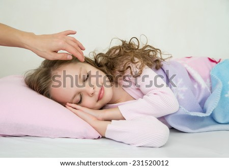 Adorable little girl sleeping in her bed. Mother's hand touching girl's head.  Nighty night! good night! - stock photo