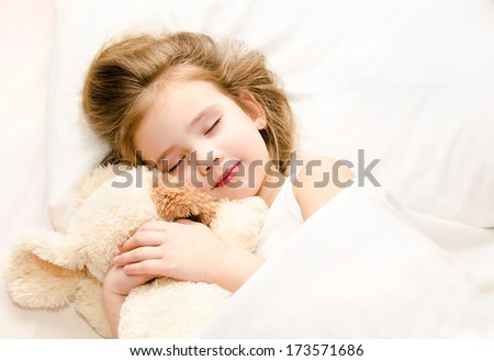 Adorable little girl sleeping in the bed with her toy  - stock photo