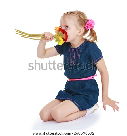 Adorable little girl smelling a bouquet of flowers - isolated on white. - stock photo