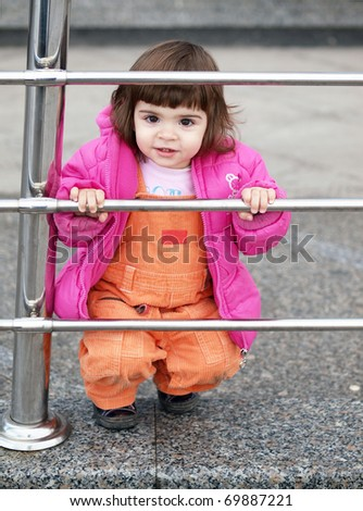 Adorable little girl smiling and holding on metal fence - stock photo