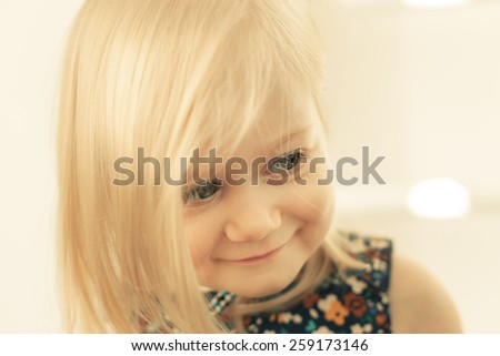 Adorable little girl smiling in front of the camera - stock photo