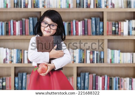 Adorable little girl standing in library while holding a book and apple - stock photo