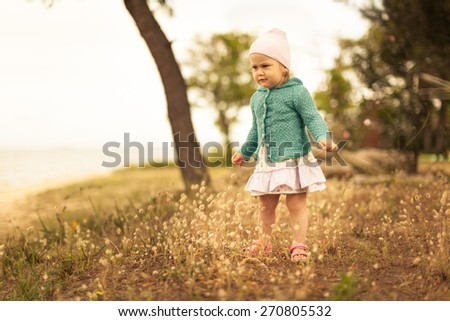 Adorable little girl standing on a meadow. Soft natural light. - stock photo
