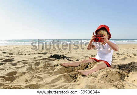 Adorable little girl takes pictures with her red camera on the beach - stock photo