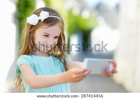 Adorable little girl taking a photo of herself with a smartphone on beautiful summer day - stock photo