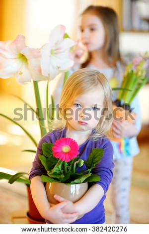 Adorable little girl taking care of plants and flowers at home