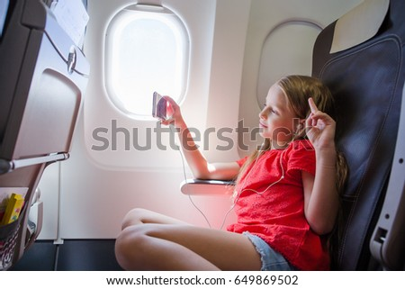 Adorable little girl traveling by an airplane. Kid sitting near aircraft window