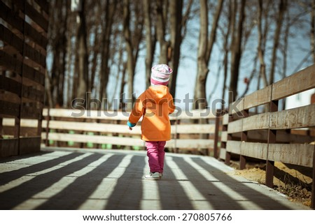 Adorable little girl walking in the park. Contrast lighting. Long deep shadows. Toned image. - stock photo