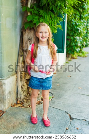Adorable little girl walking on the street, wearing bright red shoes and backpack - stock photo