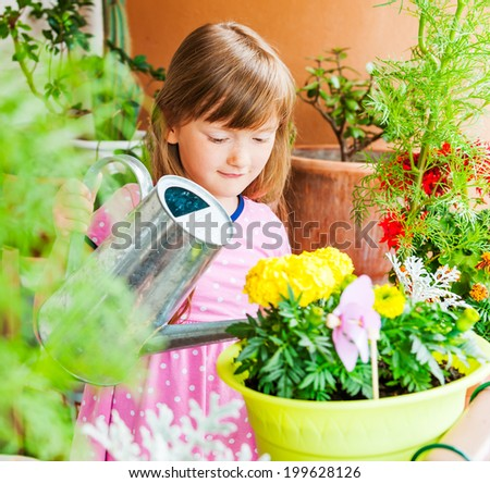 Adorable little girl watering flowers on the balcony