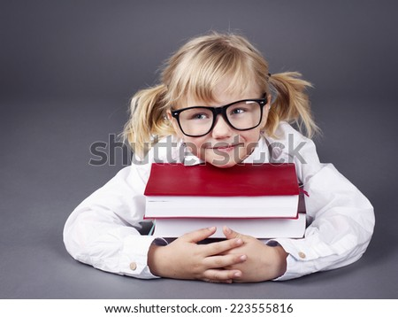 Adorable little girl wearing glasses and  holding books - stock photo