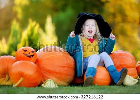 Adorable little girl wearing halloween costume having fun on a pumpkin patch - stock photo