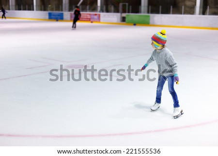 Adorable little girl wearing jeans, warm sweater and colorful hat skating on ice rink - stock photo