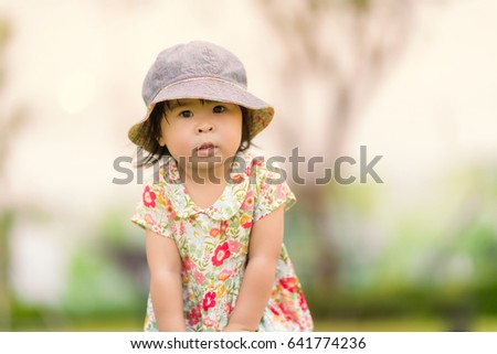 Adorable little girl wearing lovely hat playing outdoors on a very sunny day.happy kid run around in park.Explore and adventure concept