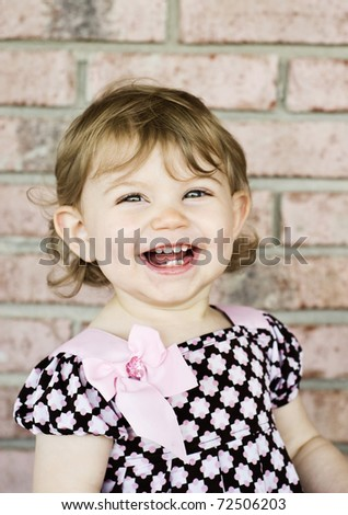 Adorable little girl with a big smile, vertical with selective focus on face and copy space - stock photo