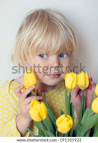 Adorable little girl with a bouquet of yellow tulips