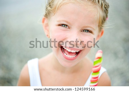 Adorable little girl with a colorful candy on tropical beach vacation