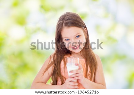 Adorable little girl with a glass of milk on a pale green background - stock photo