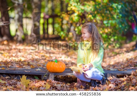 Adorable little girl with a pumpkin for Halloween outdoors at beautiful autumn day - stock photo
