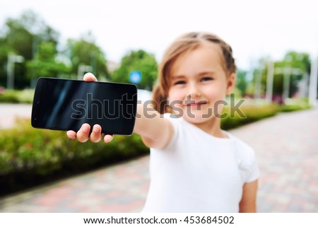 Adorable little girl with a smartphone outdoors.