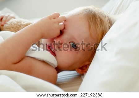 Adorable little girl with a toy bear in white bed. - stock photo