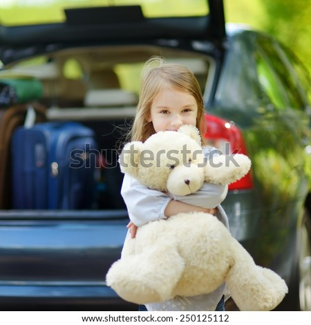 Adorable little girl with big teddy bear leaving for a car vacation with their parents - stock photo