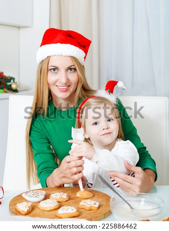 Adorable little girl with her mother baking Christmas cookies at the kitchen - stock photo