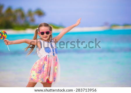 Adorable little girl with lollipop on tropical beach vacation - stock photo