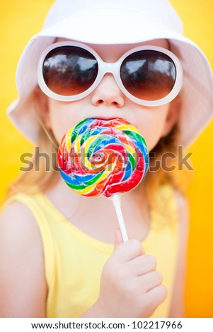 Adorable little girl with lollipop over colorful background - stock photo
