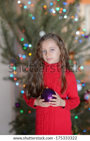 Adorable little girl with long blond hair smiling near christmas tree