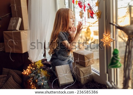 Adorable little girl with red hair in a room near the window with gifts.  children's emotions. In anticipation of the holiday - stock photo