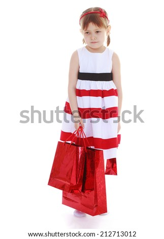 Adorable little girl with red paper bags on white background.The concept of development of the child younger years. - stock photo
