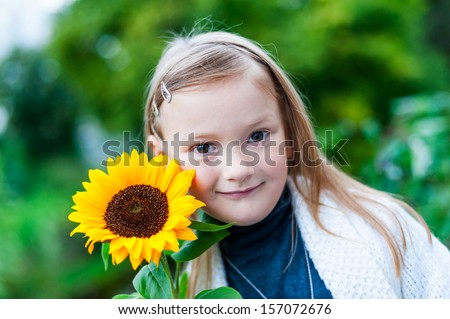 Adorable little girl with sunflower outdoors close-up
