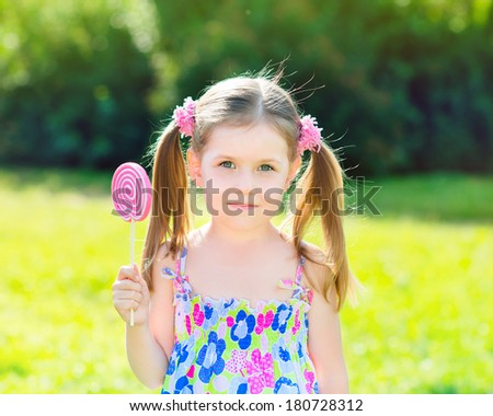 Adorable little girl with two blond ponytails holding white and pink lollipop in her hand, outdoor summer portrait - stock photo