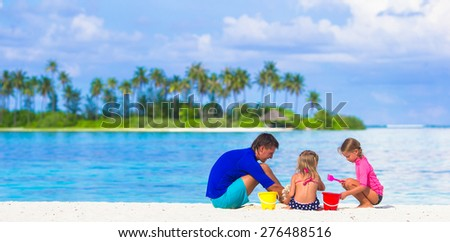 Adorable little girls and dad playing with beach toys on summer vacation - stock photo