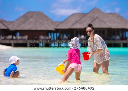 Adorable little girls and happy mother playing with beach toys on summer vacation - stock photo