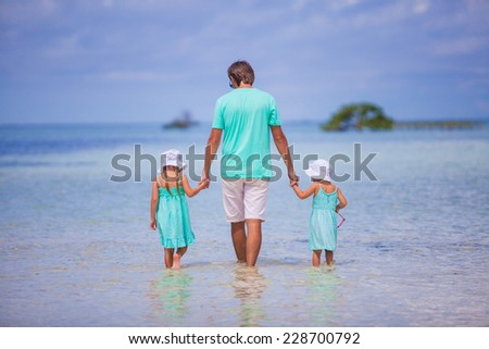 Adorable little girls and young father during beach vacation - stock photo