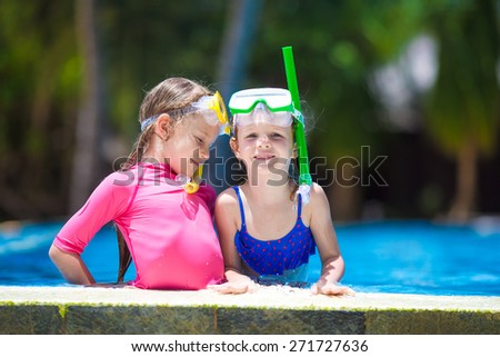 Adorable little girls at mask and goggles in outdoor swimming pool - stock photo