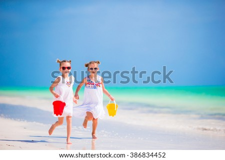 Adorable little girls have fun on the beach - stock photo