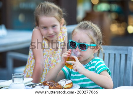 Adorable little girls having breakfast at outdoor cafe - stock photo