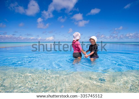 Adorable little girls having fun in outdoor swimming pool on summer vacation - stock photo