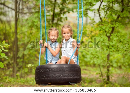 Adorable little girls having fun on a swing outdoors - stock photo