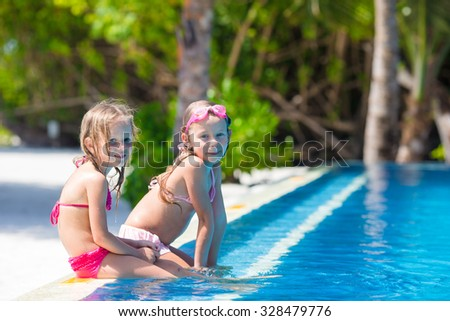 Adorable little girls in outdoor swimming pool on vacation - stock photo