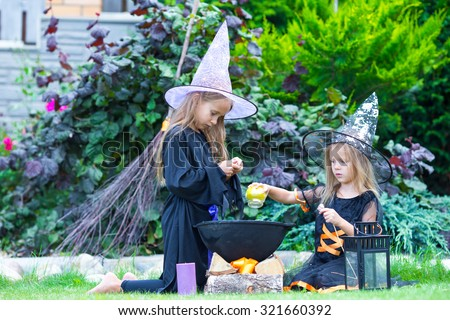 Adorable little girls in witch costume on Halloween have fun - stock photo