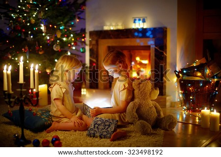 Adorable little girls opening a magical Christmas gift by a Christmas tree in cozy living room in winter - stock photo