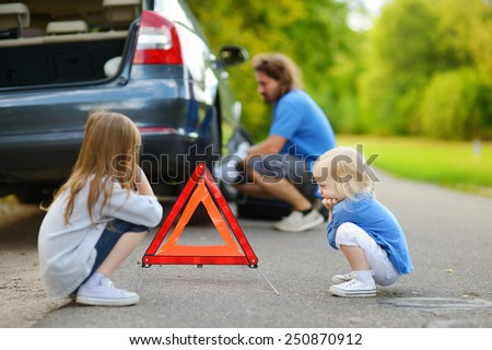 Adorable little girls waiting by the red warning triangle sign while their father is changing a car wheel outdoors on beautiful summer day