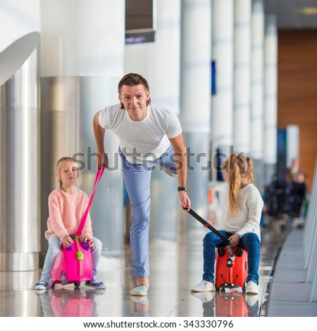 Adorable little girls with father in airport have fun waiting for boarding - stock photo